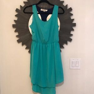 Hi-low teal dress with back cutout and navy accent